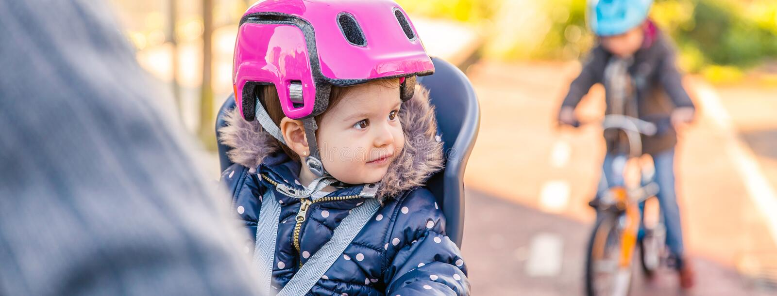 Lttle girl with helmet on head sitting in bike seat royalty free stock images