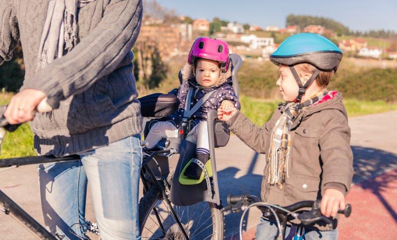 Lttlemeisje met helm op hoofdzitting in fiets stock foto's