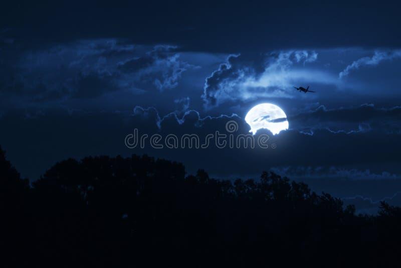 A lua brilhante ilumina o céu e Jet Aircraft comercial de aproximação imagem de stock royalty free