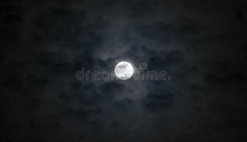 Lua cheia bonita abaixo das nuvens temperamentais wispy do cinza azul, dramat foto de stock