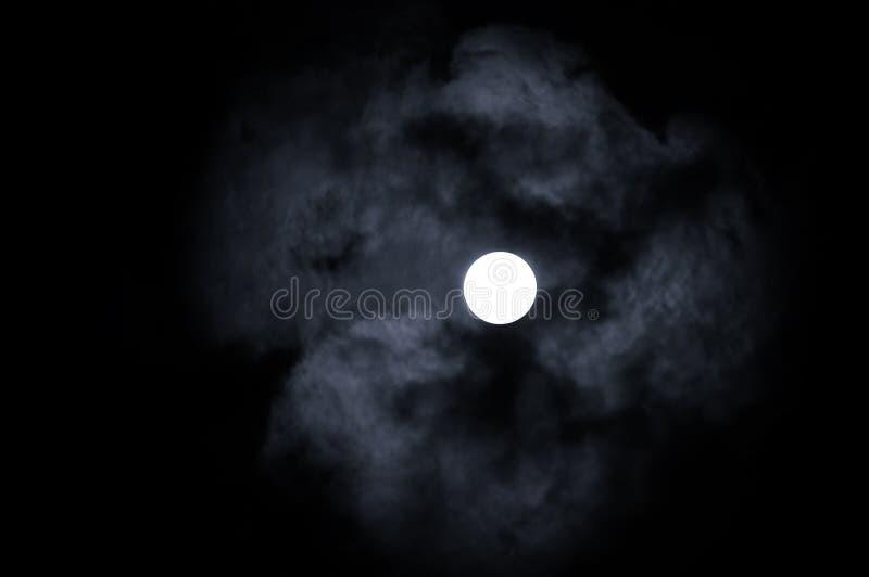 Lua cheia de brilho no céu noturno e nas nuvens de noite dramáticas - paisagem misteriosa da noite em tons frios imagem de stock