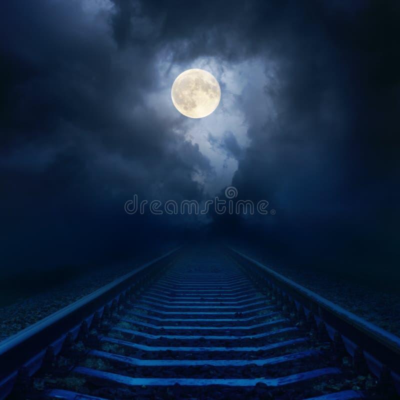 Lua cheia no céu noturno sobre a estrada de ferro fotos de stock