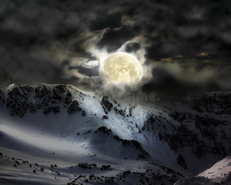 A Lua cheia no céu sobre o pico da neve da montanha fotografia de stock royalty free