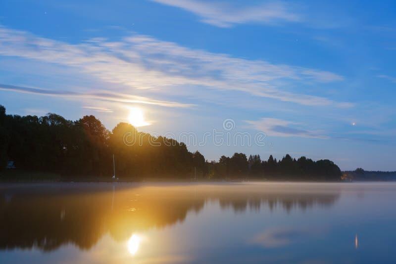 Lua cheia sobre o lago sob o céu azul imagens de stock