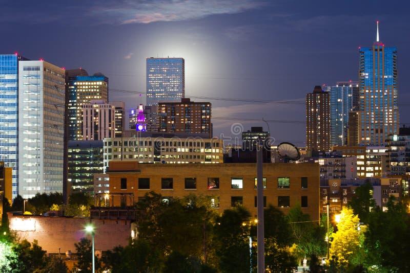 A lua de incandescência levanta-se atrás da skyline de Denver fotos de stock