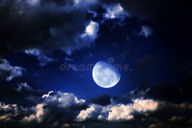 Lua e estrelas em um céu azul da noite nebulosa imagem de stock