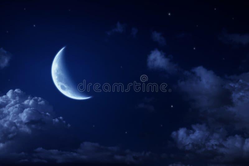 Lua e estrelas grandes em um céu azul da noite nebulosa fotografia de stock royalty free