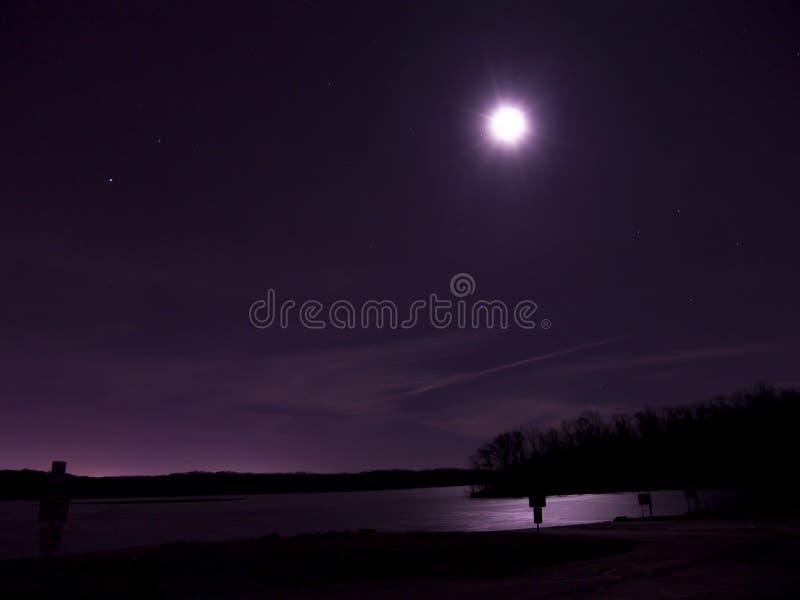 Lua e estrelas sobre o lago congelado imagens de stock