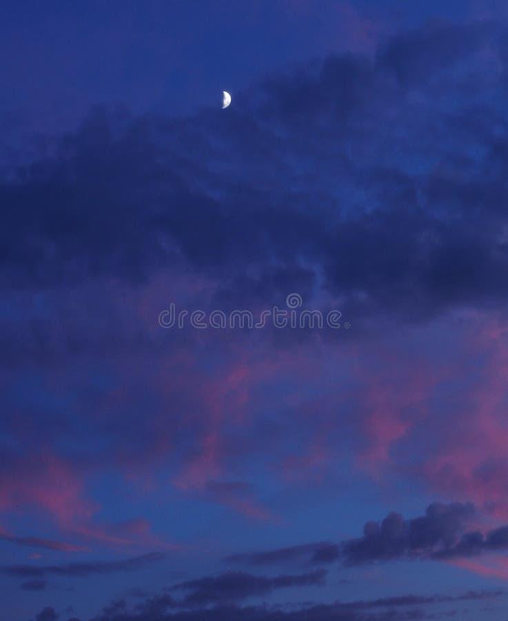 Lua e nuvens vermelhas no céu azul foto de stock royalty free