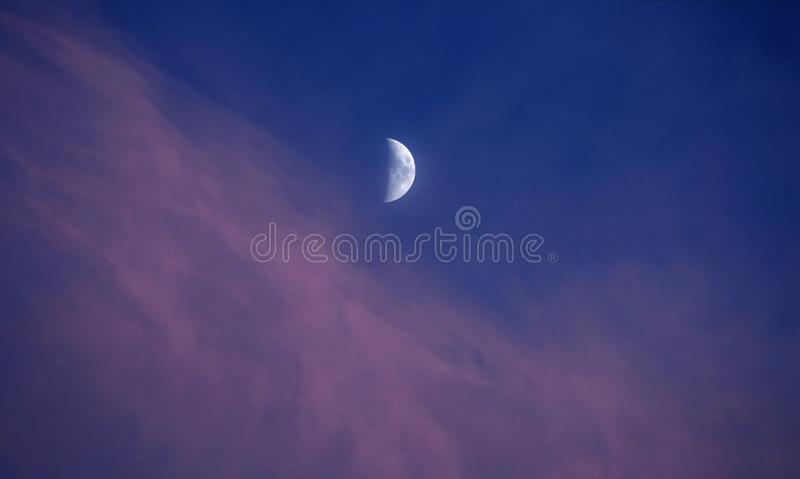 Lua e nuvens vermelhas no céu azul imagem de stock
