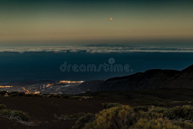 Lua eclipse 27 de julho de 2018, Tenerife Lua e Marte vermelhos perto de se imediatamente depois do por do sol Luzes da noite do  imagem de stock