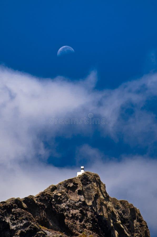 A lua está aumentando acima acima de uma casa branca pequena no monte imagens de stock royalty free
