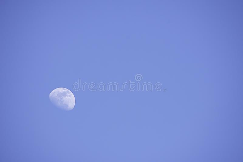 Lua na luz do dia no céu brilhante imagens de stock