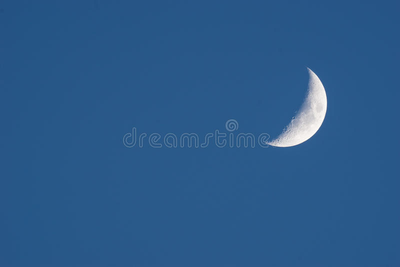 Lua nova em uma obscuridade - céu azul foto de stock royalty free
