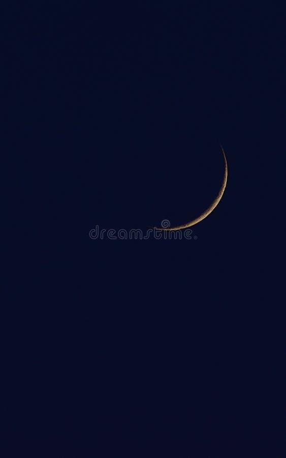 Lua nova no por do sol no céu azul imagem de stock royalty free