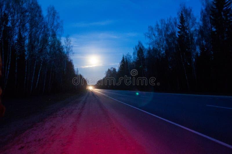 Lua sob estrelas da noite da estrada foto de stock royalty free