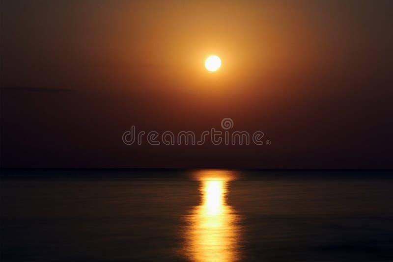 A lua super na praia A trilha da lua é refletida na água A lua da noite veio acima sobre a água Lua cheia no bea fotografia de stock royalty free