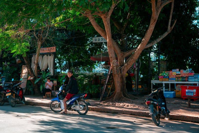 Luang Prabang, Лаос, 12 17 18: Жизнь в улицах Luang Prabang Человек стоит перед рестораном около Меконга стоковые фото