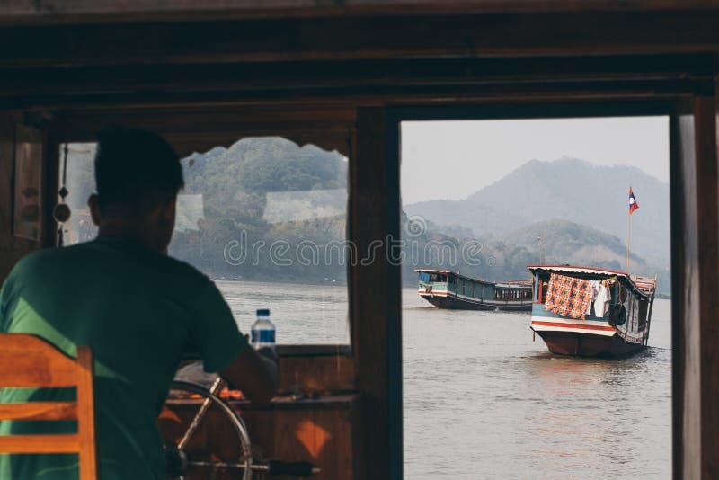 Luang Prabang, Лаос - май 2019: взгляд над лаосскими деревянными медленными шлюпками на Меконге через окно арены капитана стоковая фотография rf