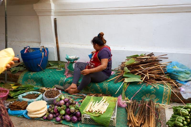 LUANG PRABANG, ЛАОС - 17-ОЕ АПРЕЛЯ 2019: Местная продавая еда на рынке утра в Luang Pra стоковое изображение