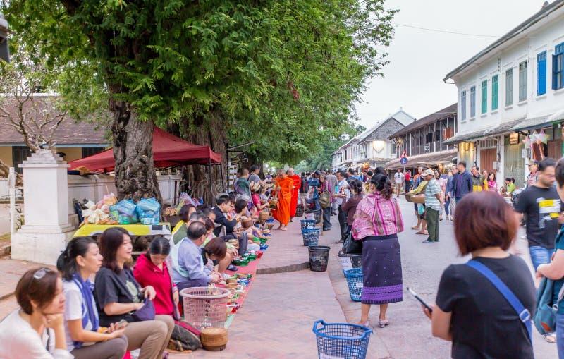 Luang Prabang, Лаос - 10-ое ноября 2017: Турист давая милостыни к стоковые изображения
