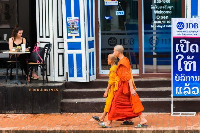 LUANG PRABANG, ЛАОС - 11-ОЕ ЯНВАРЯ 2017: Монахи на улице города Скопируйте космос для текста стоковые изображения rf