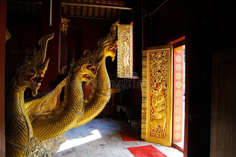 LUANG PRABANG WAT XIENG THONG, LAOS - DECEMBER 17. 2017: Dragon statues inside temple illuminated by natural sunlight stock photo