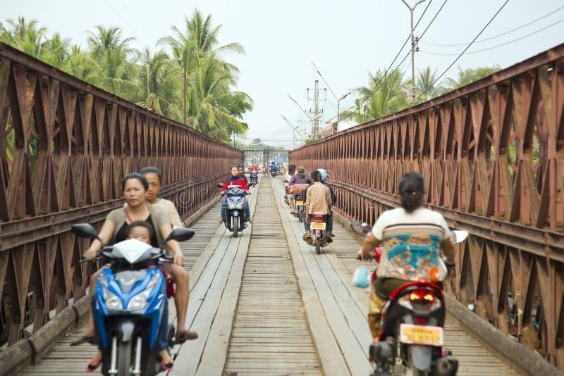 LUANG PRABANG, LAOS - ABRIL DE 2014: motos que cruzan el puente histórico del hierro fotos de archivo libres de regalías