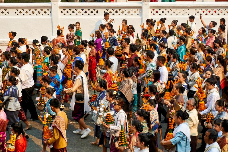 LUANG PRABANG, LAOS - APRIL 17 2019 Lokalt laotiskt folk som firar piMai Lao New Year Parade festival royaltyfri fotografi