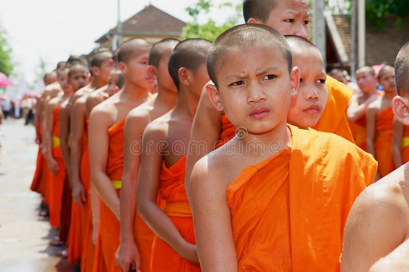 Young monks take part in the religious procession during Lao New Year celebration in Luang Prabang, Laos. Luang Prabang, Laos - April 16, 2012: Unidentified royalty free stock photo