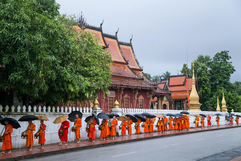 Luang Prabang, Laos - circa agosto 2015: Elemosine tradizionali che danno cerimonia di alimento di distribuzione ai monaci buddis immagini stock libere da diritti