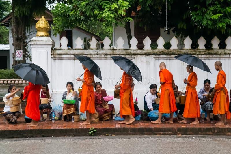 Luang Prabang, Laos - circa agosto 2015: Elemosine tradizionali che danno cerimonia di alimento di distribuzione ai monaci buddis immagine stock libera da diritti