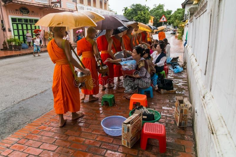Luang Prabang, Laos - circa agosto 2015: Elemosine tradizionali che danno cerimonia di alimento di distribuzione ai monaci buddis fotografia stock libera da diritti