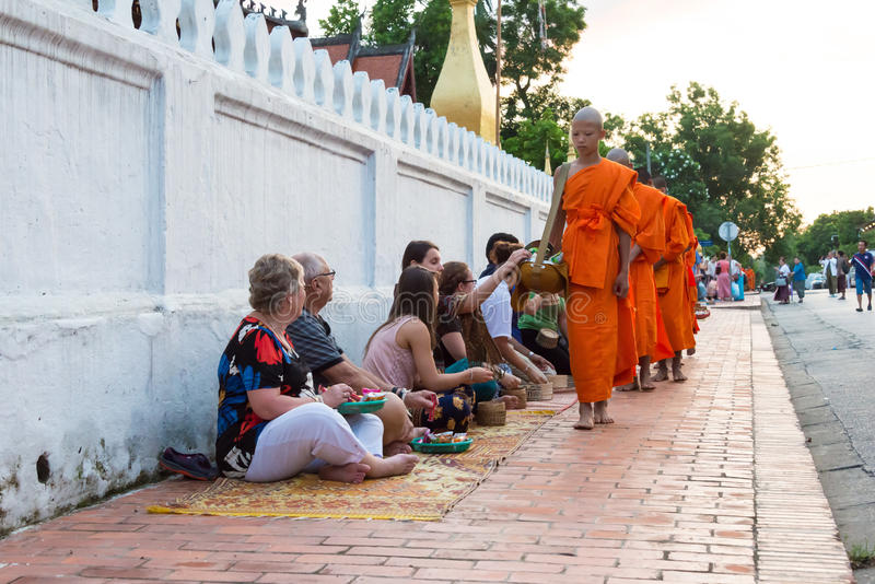Luang Prabang, Laos - 13 de junio de 2015: Limosnas budistas que dan ceremonia foto de archivo libre de regalías