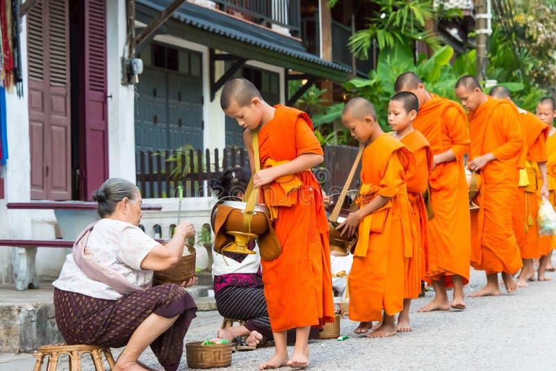 Luang Prabang, Laos - 13 de junio de 2015: Limosnas budistas que dan ceremonia foto de archivo