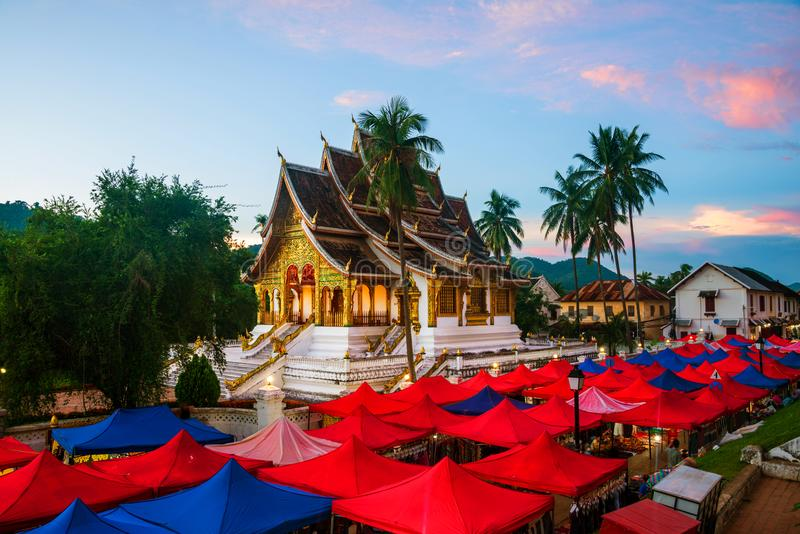 Famous night market in Luang Prabang, Laos with illuminated temple and sunset sky stock photos