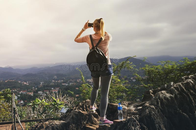 LUANG PRABANG, LAOS - 29 JUNE 2018 - Asian female tourist takes picture of sunset on top of Phousi mountain in Luang Prabang, Laos. Female tourist takes picture royalty free stock photo