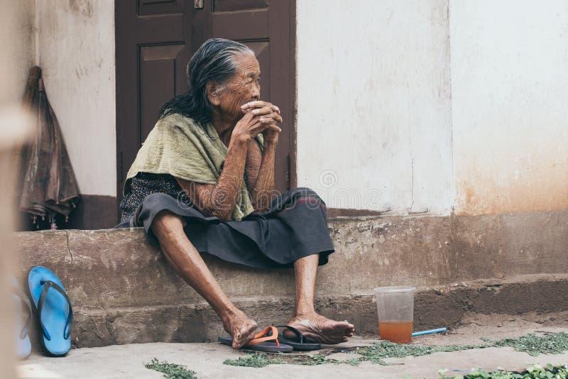 Luang Prabang, Laos - Maj 2019: den gamla laotiska kvinnan sitter på husfarstubron, fundersam blick arkivfoto