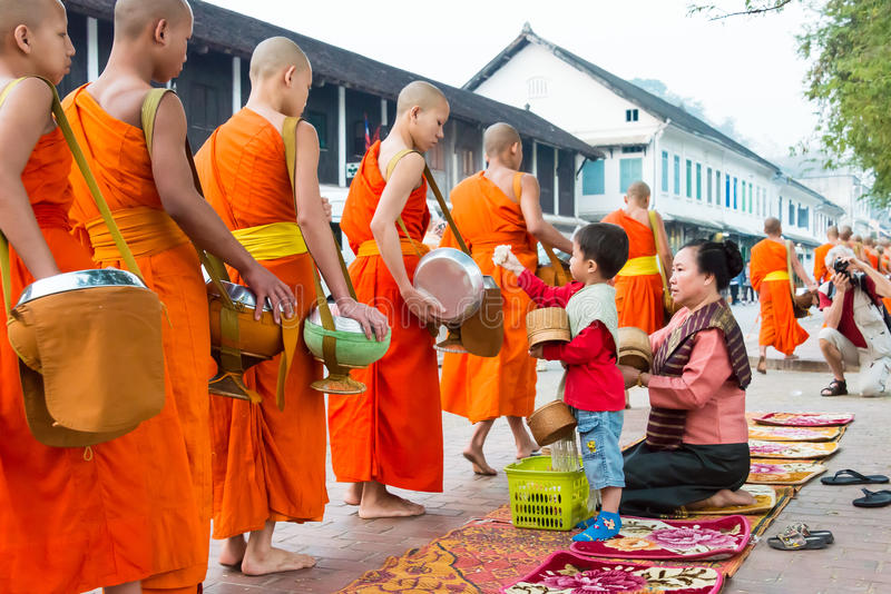 Luang Prabang, Laos - Mar 05 2015: Buddhist monks collecting alms in the morning. The tradition of giving alms to monks in royalty free stock photos