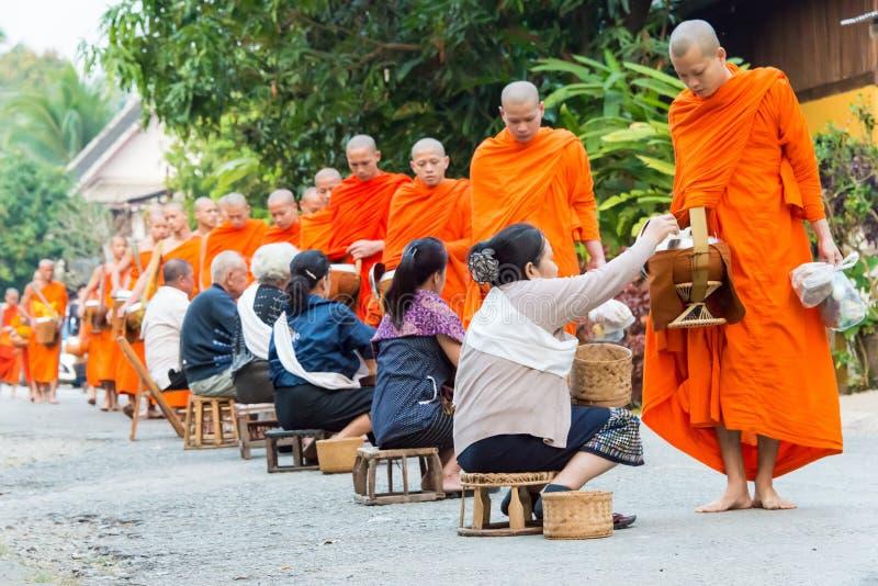 Luang Prabang, Laos - 6 mars 2015 : Moines bouddhistes rassemblant l'alm images libres de droits