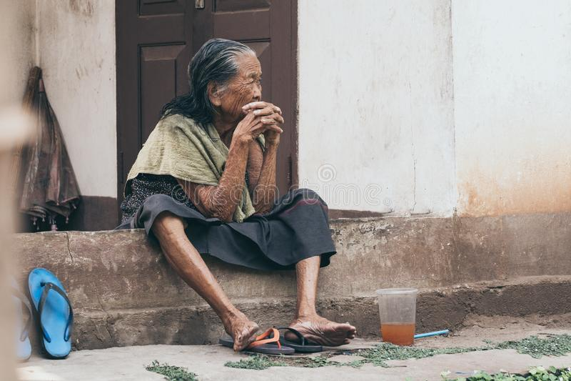 Luang Prabang, Laos - Mei 2019: de oude vrouw van Laos zit op de huisportiek, nadenkende blik stock foto
