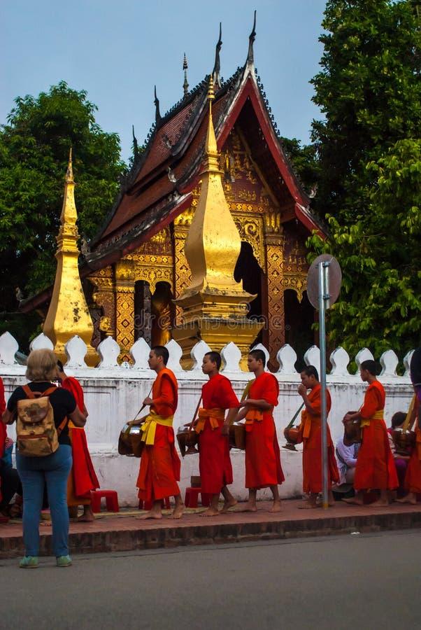 Luang Prabang, Laos - November 22, 2015: Allmosa som framme ger ceremoni av Wat Xieng Thong royaltyfri fotografi