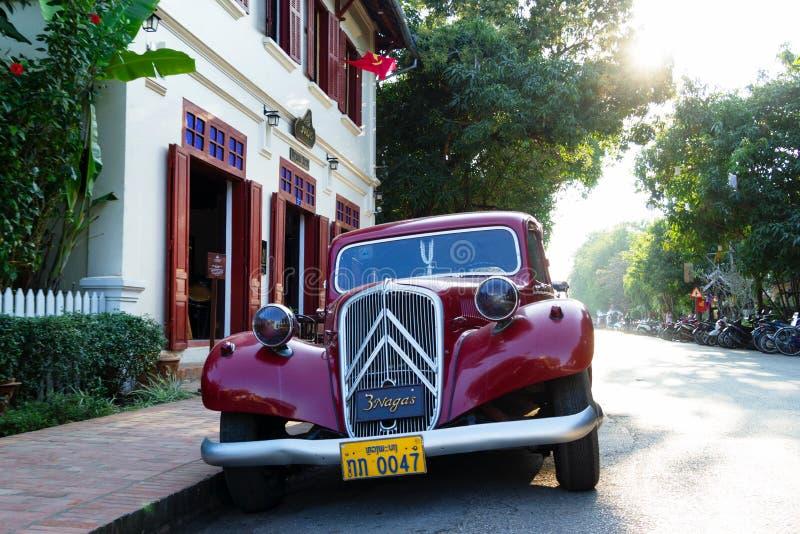 LUANGPRABANG, LAOS - JANUARI 16, 2018: Mening over een klassieke retro rode auto op een dichtbij geparkeerde straat aan restauran stock fotografie