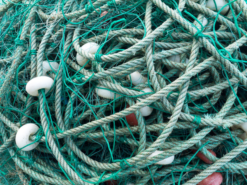 LUARCA, SPAIN - DECEMBER 4, 2016: Green fishing net with white f. Loats at the fish market pier in Luarca, Spain royalty free stock images