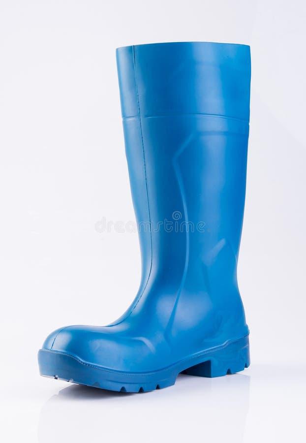 but lub błękitnego koloru gumowi buty na tle fotografia royalty free