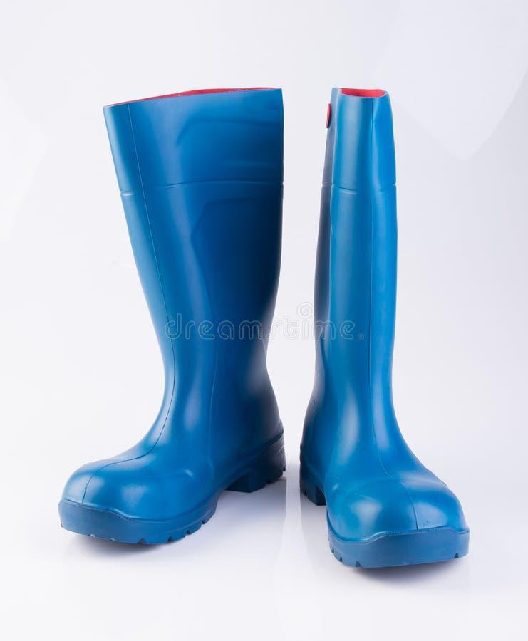 but lub błękitnego koloru gumowi buty na tle fotografia stock