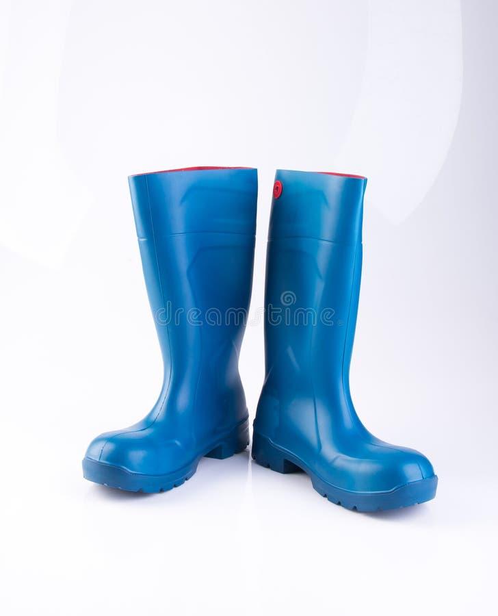 but lub błękitnego koloru gumowi buty na tle obraz royalty free