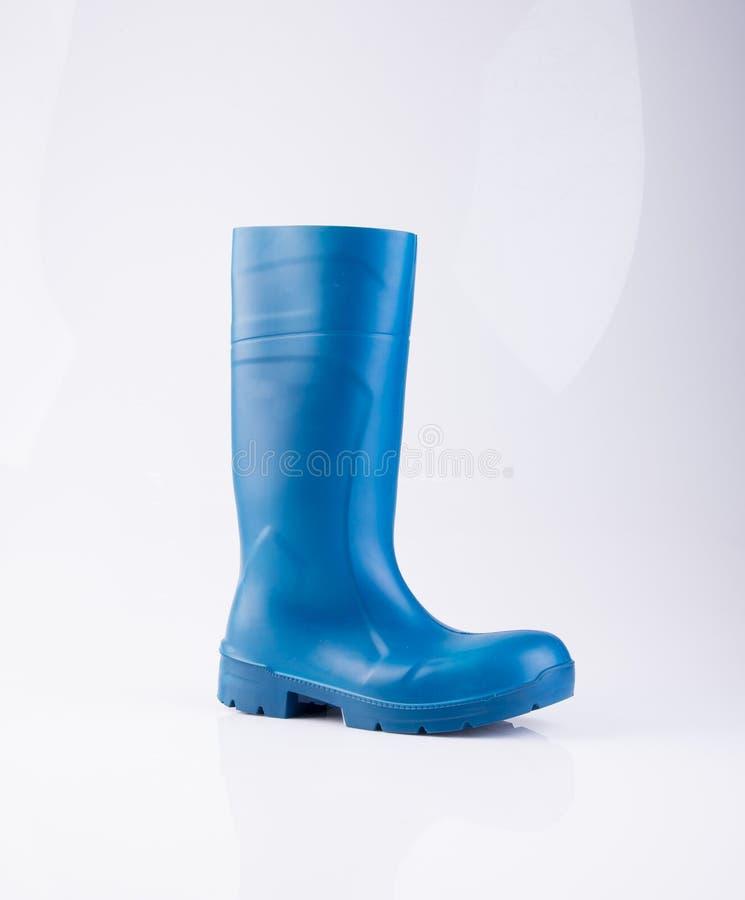 but lub błękitnego koloru gumowi buty na tle obraz stock