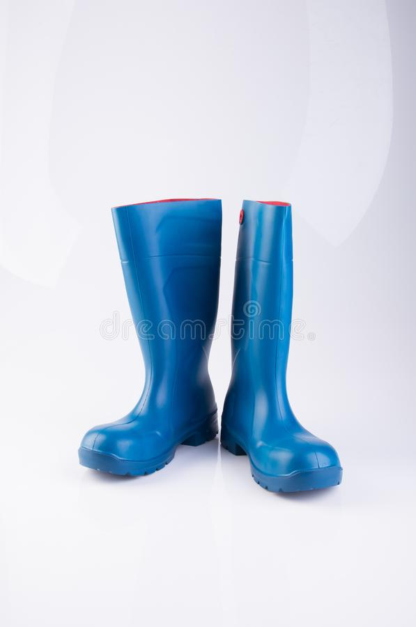 but lub błękitnego koloru gumowi buty na tle obrazy stock