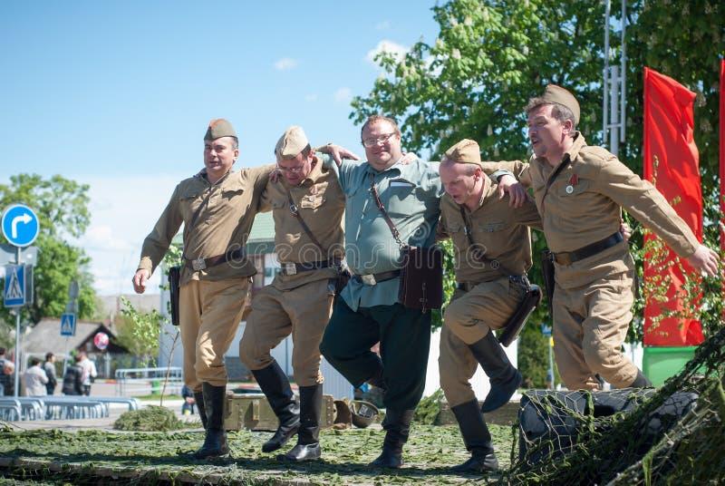 LUBAN, БЕЛАРУСЬ - 9-ОЕ МАЯ 2015: группа в составе люди в форме советских солдат выполняя танец стоковое фото